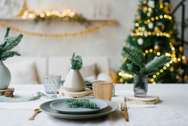 Украшен новогодний стол в светло-бирюзовых тонах. вазы с еловыми ветками на фоне гирлянды