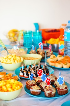 Украшенный праздничный стол с различными десертами и закусками