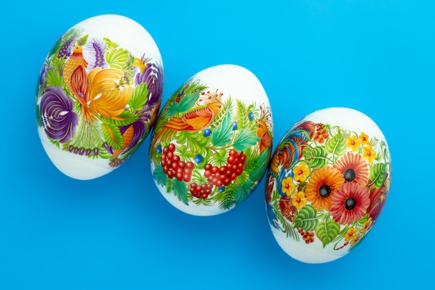 Decorated paschal chicken eggs on blue background. easter colored gift card.
