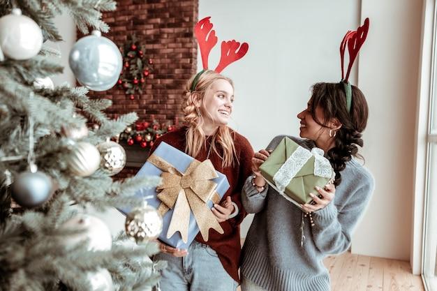 장식 된 선물. 내부 선물 포장 상자를 들고 축제 방식으로 춤추는 행복 유치 소녀 크리스마스 개념