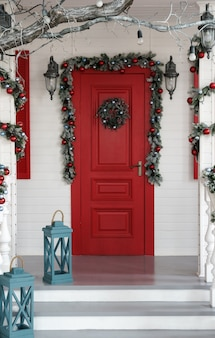 Decorated red door for christmas holidays with blue lanterns on the stairs