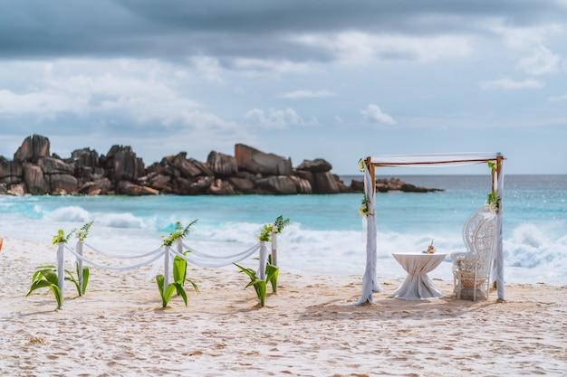 Украшенная романтическая свадебная обстановка со столом и стульями на песчаном тропическом пляже в свете заката с угрюмыми облаками, сейшельские острова.
