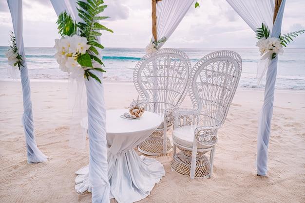 Украшенная романтическая свадебная обстановка со столом и стульями на песчаном тропическом пляже с океаном и облачным небом, сейшельские острова.