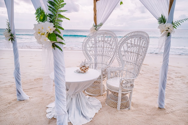 Decorated romantic wedding setting with table and chairs on sandy tropical beach with ocean and cloudy sky, seychelles islands.