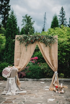 Decorated in rustic style wedding arch for a beautiful ceremony