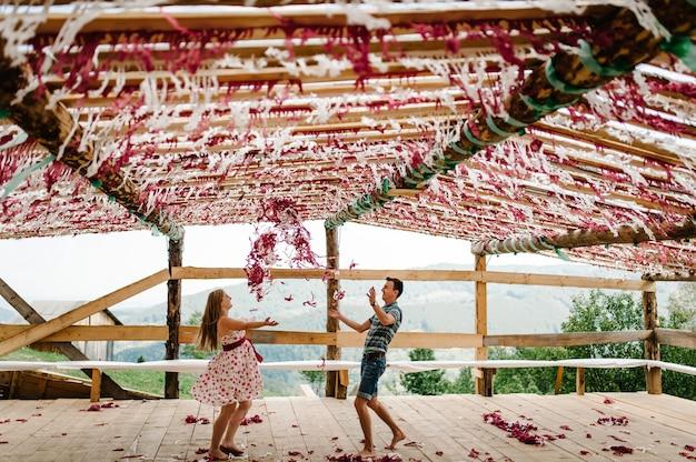 Украшенный шалаш, палатки, палатка, тент, навес, сцена. танцевать. свадьба. беременная женщина, муж бросает красный, белый декор бумага конфетти, босиком. круглый живот. природа, парк, лес, гора