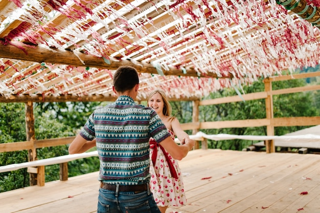 Decorated shalash, tents, tent, awning, canopy, scene, red, white decor paper, confetti. wedding. pregnant woman, husband dancing. round belly. nature, park, forest, mountain, stylishly, nine month