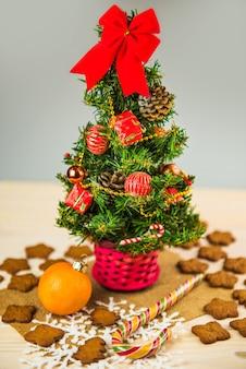 Украшенная маленькая рождественская елка, изолированная с пряниками и сладостями на деревянном фоне