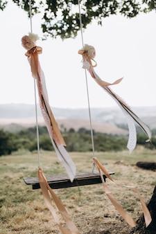 Украшенные качели с красивыми лентами, подвешенными к дереву