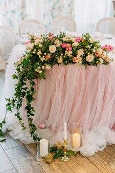 花とキャンドルで作られたアレンジメントで結婚披露宴の装飾されたテーブル