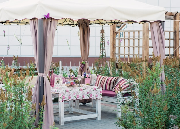 Decorated table for a cafe in the open area, pink tones, parisian atmosphere, tents