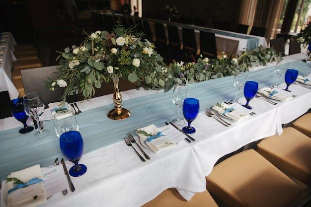結婚式のお祝いのための装飾されたテーブル。たくさんの窓がある明るいレストラン。