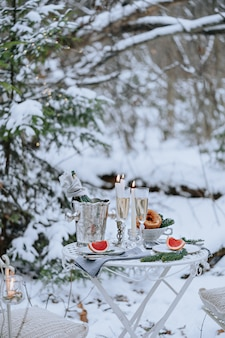Decorated table for a romantic dinner with candles, sparkling wine and fruit in the winter forest
