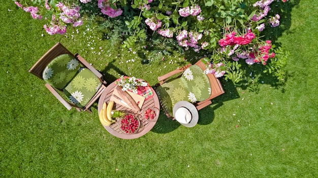 Decorated table with bread, strawberry and fruits in beautiful summer rose garden, aerial top view of romantic date table food setting for two from above
