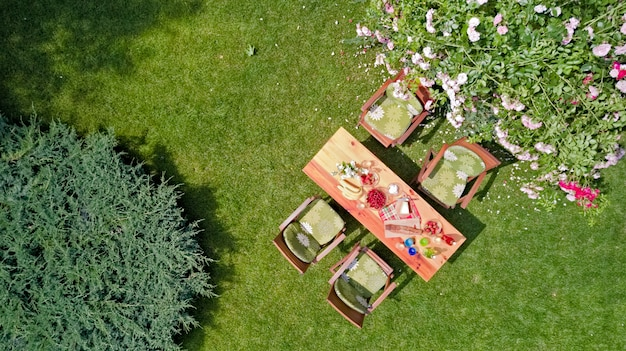 Decorated table with cheese, strawberry and fruits in beautiful summer rose garden, aerial top view of table food and drinks setting outdoors from above.