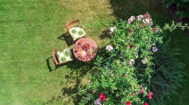 Украшенный стол с сырами, клубникой и вином в прекрасном розарии, вид сверху на романтическое свидание, сервировка стола для двоих сверху