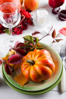 Decorated table with pumpkin and candleholder.
