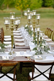 Decorated wedding celebration table on the grass with guests seats outdoors in the gardens with burning candles