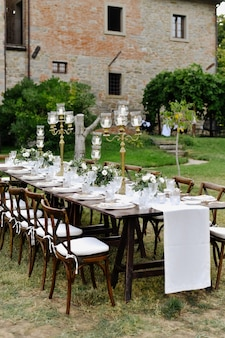 Decorated wedding celebration table with guests seats outdoors in front of old building made of stone