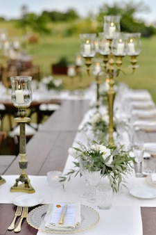Decorated wedding celebration table with guests seats outdoors in the gardens with burning candles