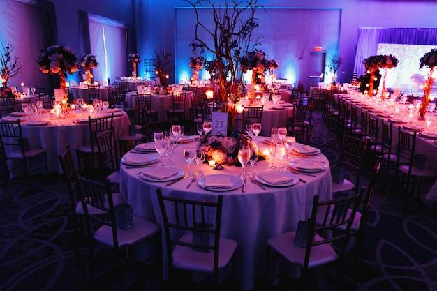양초, 원형 테이블 및 중앙 장식으로 꾸며진 웨딩 홀