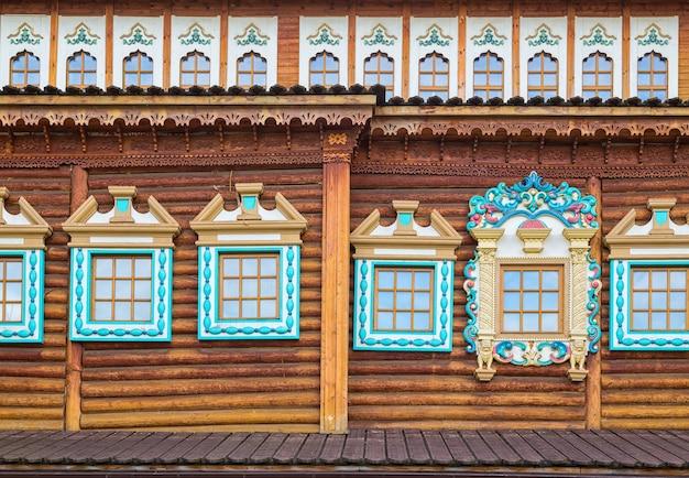 Декорированные окна в старом бревенчатом доме. русская традиционная архитектура. деревянный дворец царя в парке коломенское, москва, россия.