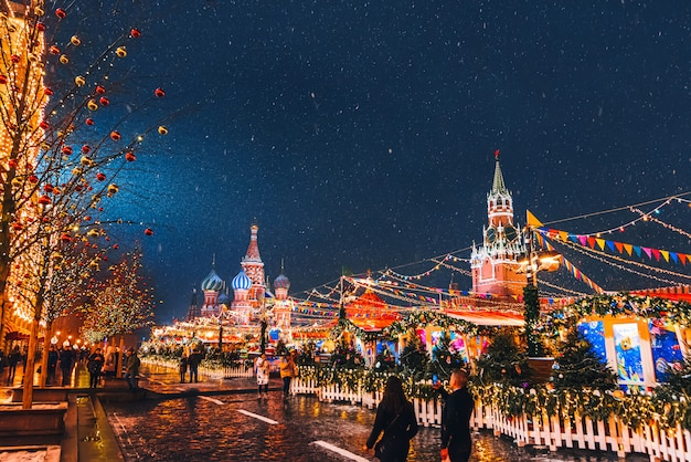 Decorated with christmas decor red square in moscow with st. basil's cathedral and the spasskaya tower at night in winter