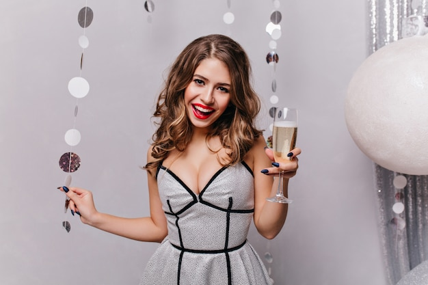 Decorated with christmas toys, young lady smiling and having fun, wearing beautiful festive dress and holding glass of sparkling wine in her left hand