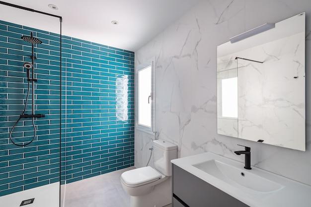 Современная ванная комната, облицованная плиткой, оформлена в темных аквамариновых и белых тонах, с душевой зоной, новая раковина и туалет.
