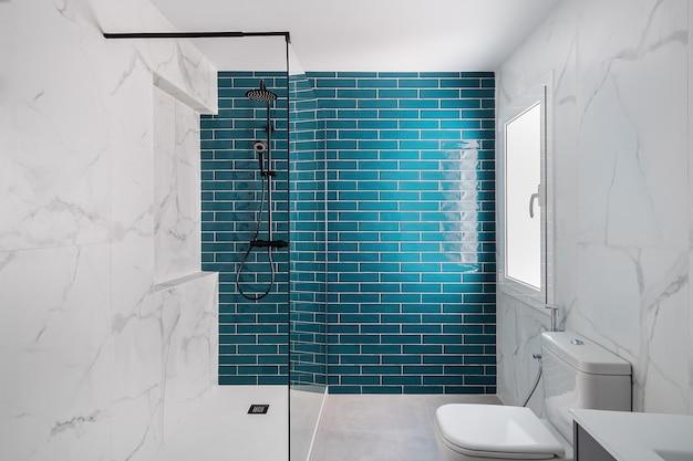 Современная ванная комната, облицованная плиткой, оформлена в темных аквамариновых и белых тонах, с душевой зоной, новой раковиной и ...