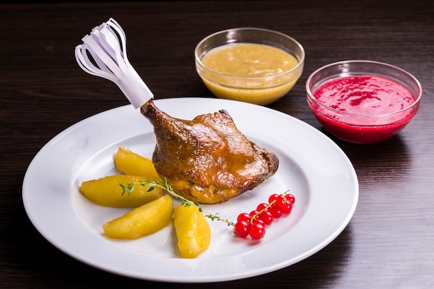 Decorated with duck leg garnished with roasted potatoes with sauce