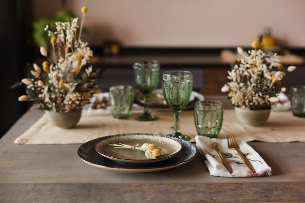 花で飾られ、さまざまな食器のディナーテーブル(セラミックプレート、ワイングラス、カップ、フォーク、ナイフ)が提供されます
