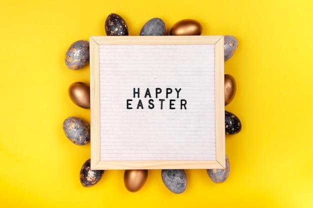 Украшен золотыми пасхальными яйцами и доской для писем «счастливой пасхи» на ярко-желтом праздничном фоне. горизонтальный вид сверху copyspace