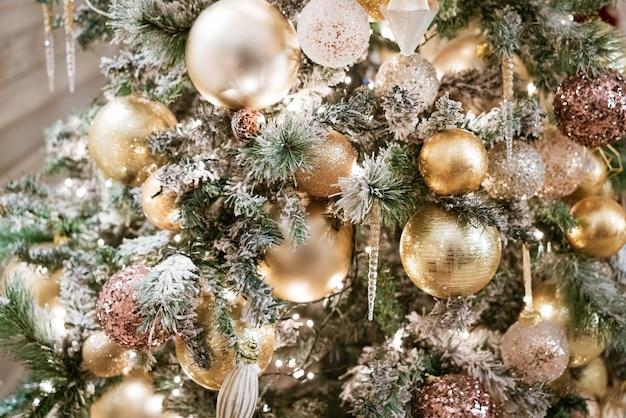 Украшенные золотыми шарами и прозрачными сосульками ветки елки в вечернее время ...