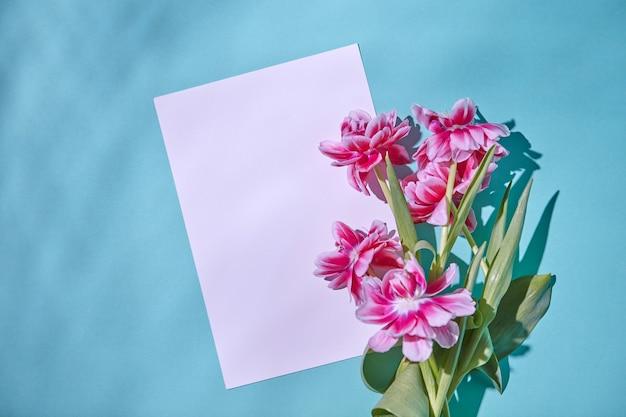 影の反射と緑の葉とピンクの新鮮なチューリップで飾られた