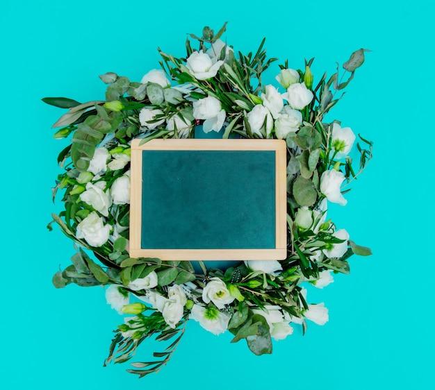 青い背景に白いバラと黒板で飾られた花輪。飾られた。上図
