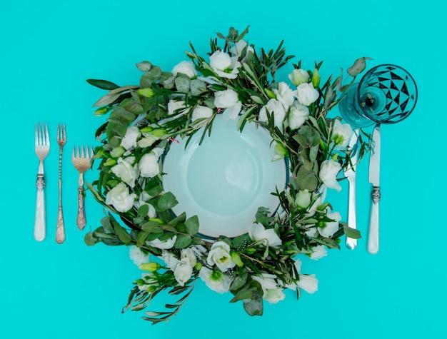 緑の背景に白いバラとカトラリーで飾られた花輪。飾られた。上図