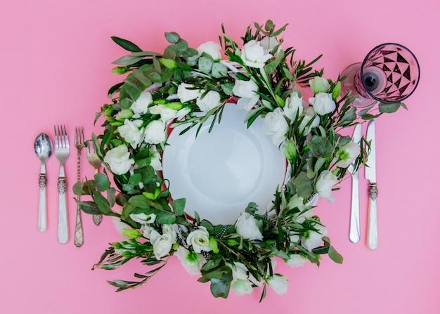 ピンクの背景に白いバラとカトラリーで飾られた花輪。飾られた。上図