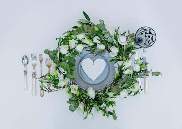 白い背景に白いバラとカトラリーで飾られた花輪。飾られた。上図