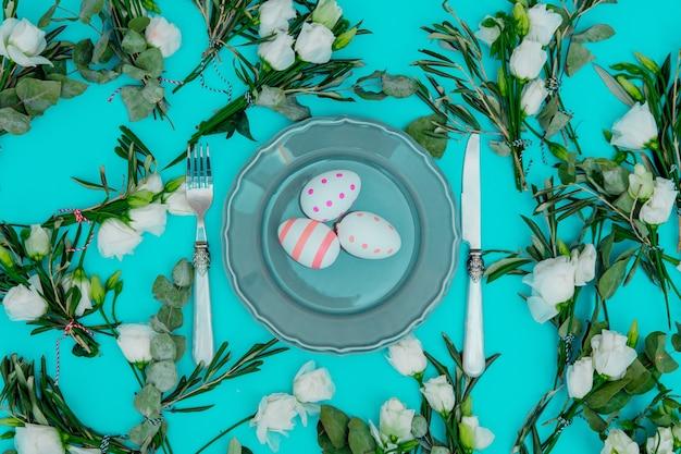 緑の背景に白いバラとイースターエッグのカトラリーで飾られた花輪。飾られた。上図