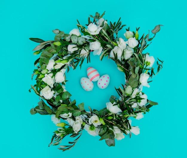 青い背景に白いバラとイースターの卵で飾られた花輪。飾られた。上図