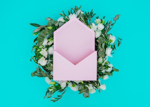 青い背景に白いバラとピンクの封筒で飾られた花輪。飾られた。上図