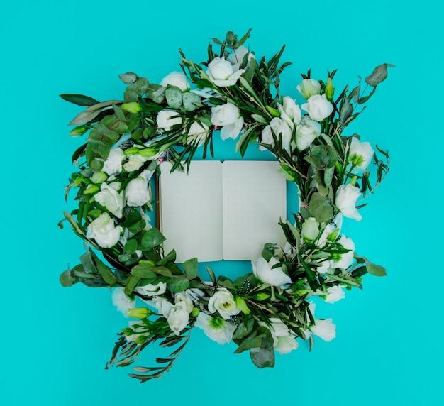 青い背景に白いバラとレシピノートで飾られた花輪。飾られた。上図