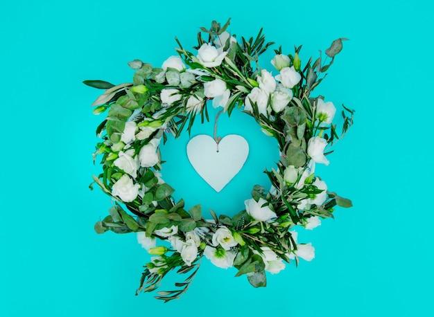 青い背景に白いバラのハート型の愛で飾られた花輪。飾られた。上図