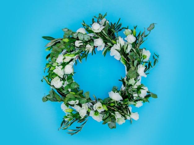 青い背景に白いバラで飾られた花輪。飾られた。上図