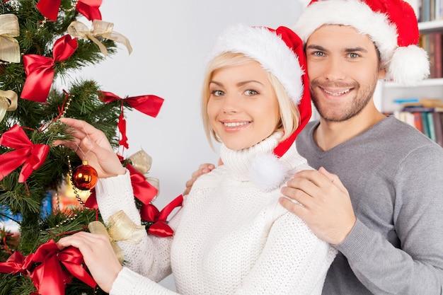 함께 크리스마스 트리를 장식합니다. 함께 크리스마스 트리를 장식하는 쾌활한 젊은 부부