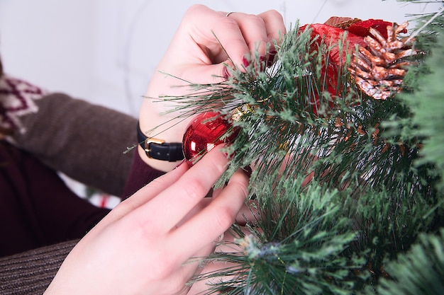 Decorating christmas tree at home. hand holding red ball