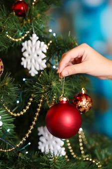 明るい背景にクリスマスツリーを飾る Premium写真