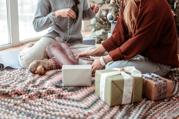 プレゼントを飾る。床に座ってラッピングするために珍しい素材を使用して勤勉で快適な女性クリスマスのコンセプト
