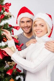 크리스마스 장식 트리. 크리스마스 트리를 장식하고 카메라를 보며 웃고 있는 쾌활한 젊은 부부의 상위 뷰